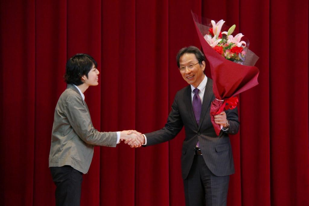 新入生代表の荏原さんから花束を受け取る姜先生