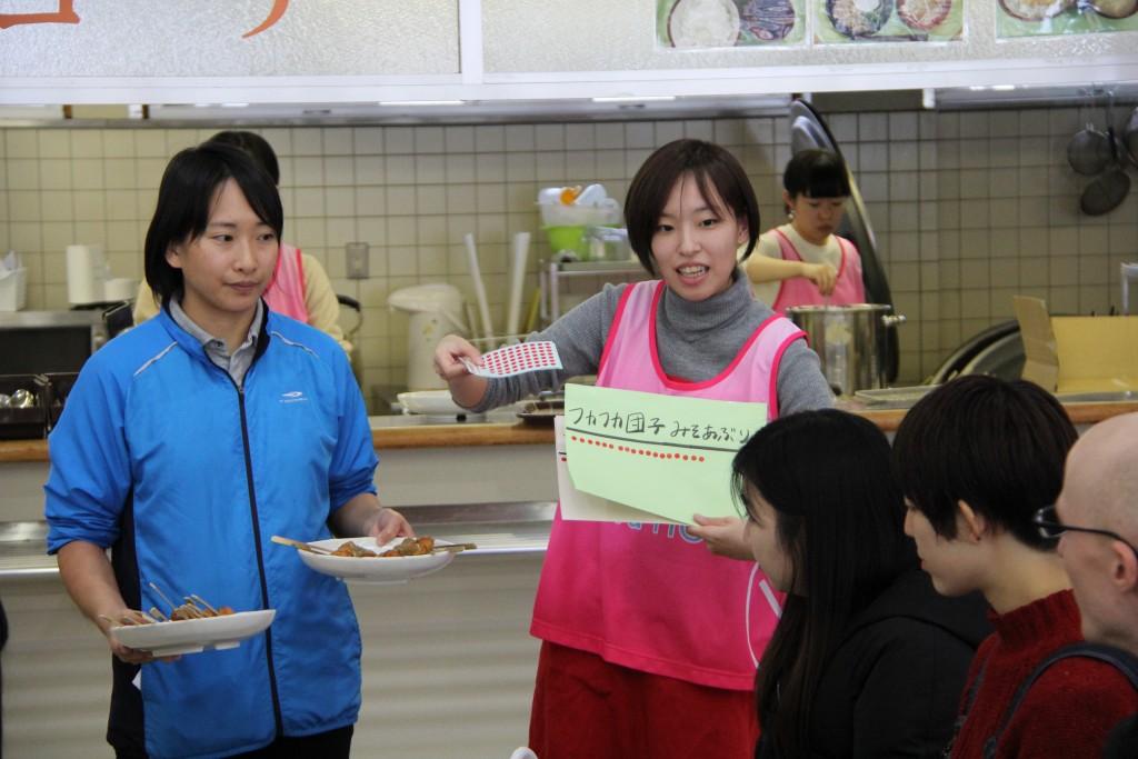 「復興雑煮」の説明をする朝妻さん(右)