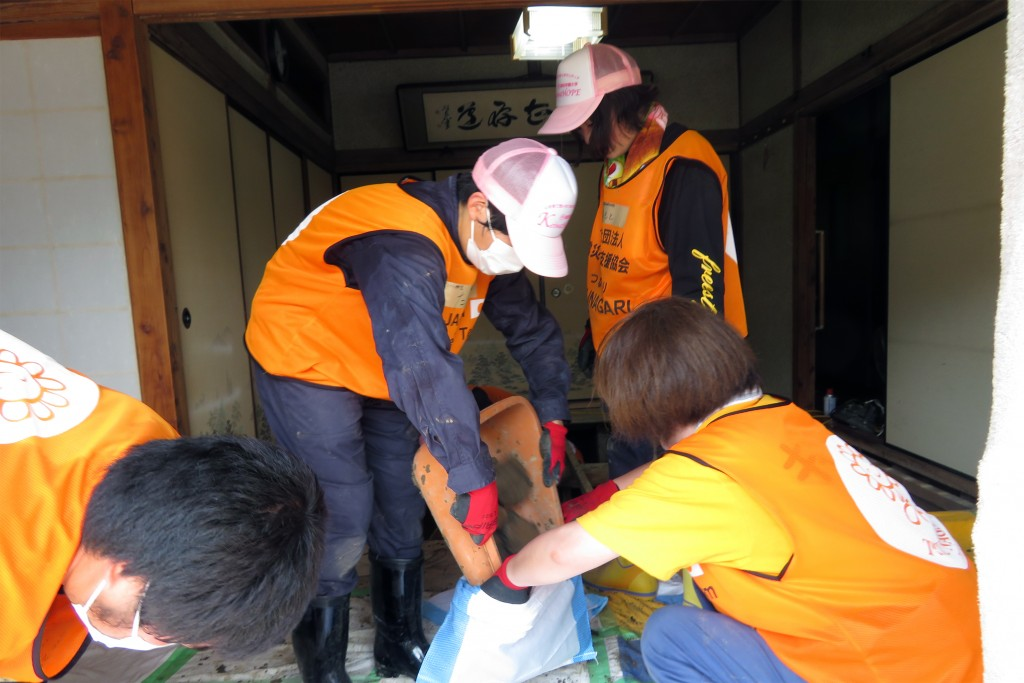 清掃で出た泥を集める(写真左から2人目が谷井さん)