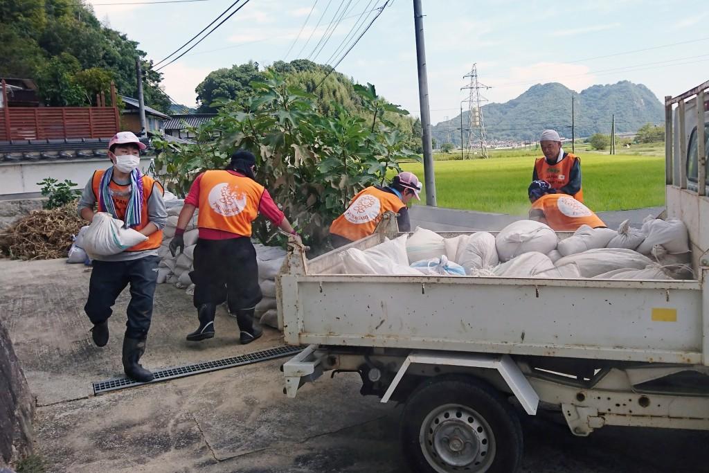 集まった泥をトラックで運ぶ(写真左が結城さん)