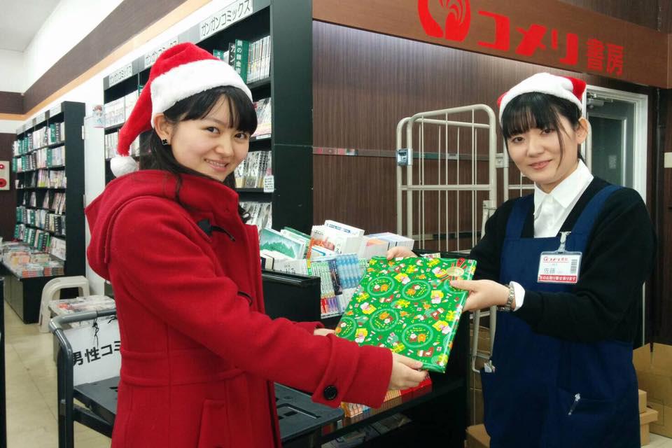 書店から本を受け取る川崎さん(写真左)
