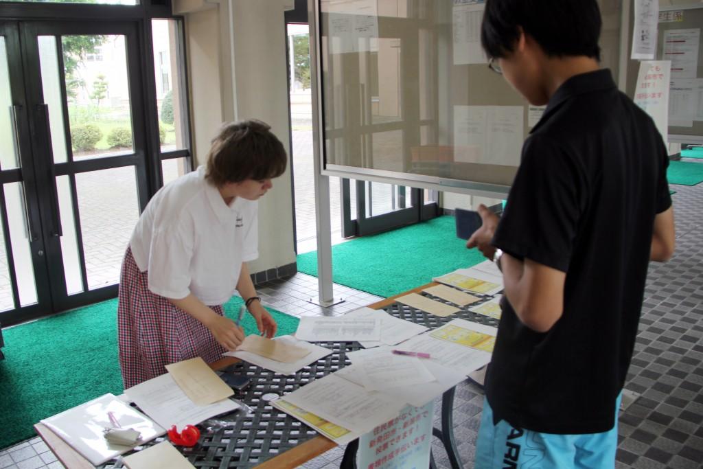 不在者投票宣誓・請求書類の作成方法を説明する学生たち